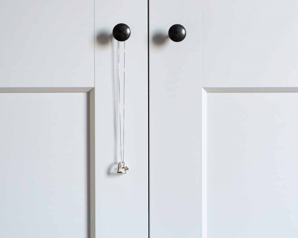 White wardrobe doors with a hanging necklace with silver heart pendant. Minimalistic style.