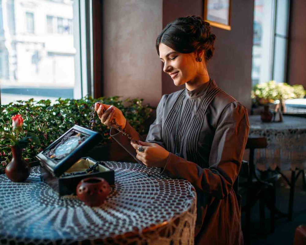Young happy woman in cafe with casket and jewelry. Portrait of beautiful young retro lady with beads in her hands. Smiling brunette in vintage dress sitting in cafe.